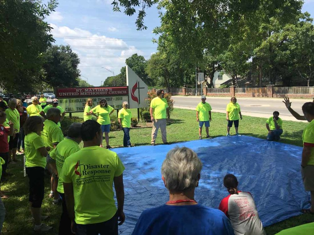 volunteers learn the proper technique for placing a tarp on a roof during early response team training in san antonio