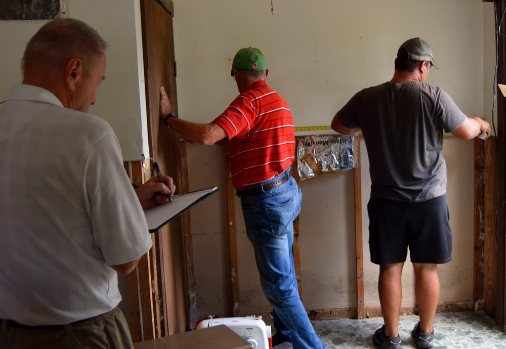 Members of Oak Hill UMC measure a home so they know how much material to bring.