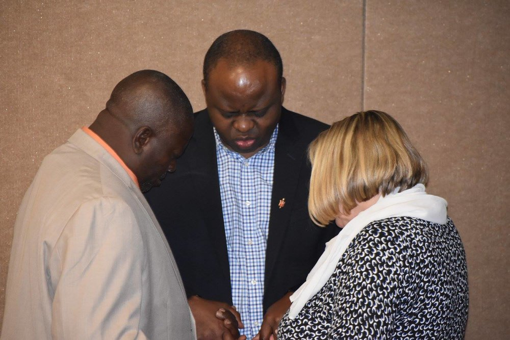 Commission members praying together during their latest meeting.
