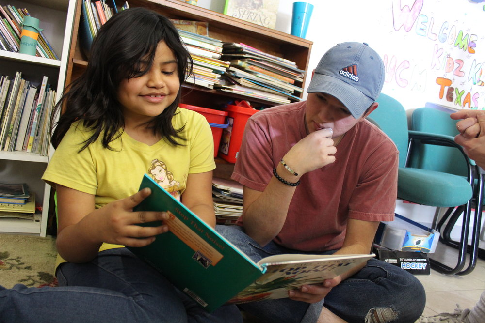 Texas State education student Evan Perez reads with an elementary student. Photos by Consolatrice Nzoya