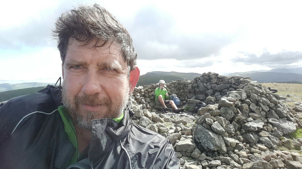 Like my new do? Pete sheltering in a rock Cain at the top of the hill while we have a bite to eat.