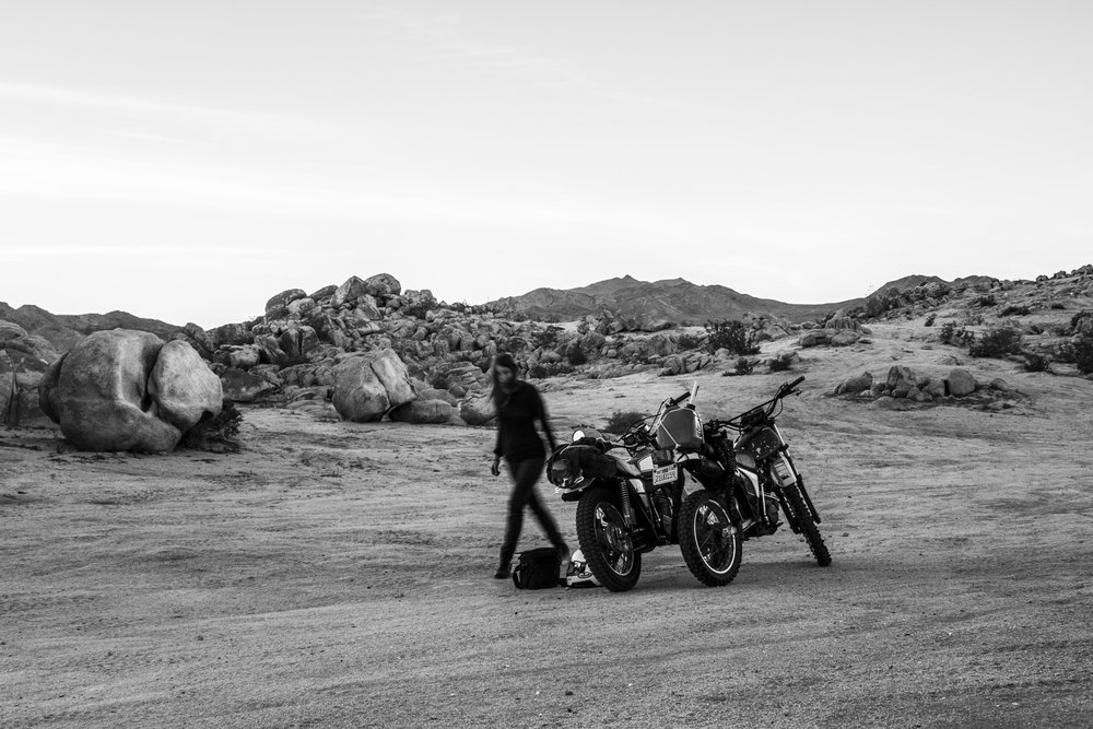 """Horizon Parallel  Flame, Motorcycles 70' x 10"""" x 10""""  The Mojave Desert is a place the American psyche has turned it's heart to, a unique place in our personal mythology. The poetry of the harshest and most rugged terrain upon which some of our go west, rugged individualism, survivalist identity has been formed. The vastness, the quiet, the trackless landscape. The playas, dried remnant of a prehistoric time are symbol to the ever changing, and the slow timescale of the earth. There is an open story of abstraction and projection alongside the prehistoric remnants that makeup the Mojave. This famous California desert has the perfect intersection between off-road culture, speed trials and earth art, both in it's history and also it's present. I was inspired, and I wanted to work on a sculpture that dialogued with this mythopoetic space.  It only seemed fitting to create this piece out in the backcountry, taking a journey and setting out to see if I could find one of those iconic vast Mojave canvases that was that was blank, unpaved, off road and not accessible by anything but bike. This place existed in my mind, but I had to go find it.  Riding out into backcountry is tough. You aren't really going fast. You're in soft sand and picking your way through it. We were riding vintage enduros back there. And one of the bikes was from '74. These bikes are different, they are heavier and they don't handle like a modern dirtbike. But that's the way it is out in the wild. Everything depends on you, having enough water, knowing how to read the weather, how to backtrack and know your orientation, how to stay warm, make your own light and so on. That is survival, you really have to learn to depend on yourself, but that feeling of independence, and ultimately interdependence with the earth, is really in my opinion, one of our most fundamental powers and a very real source of joy.  We were all packed up over the back of the bikes. And that's why I love those bikes - they are tough a"""