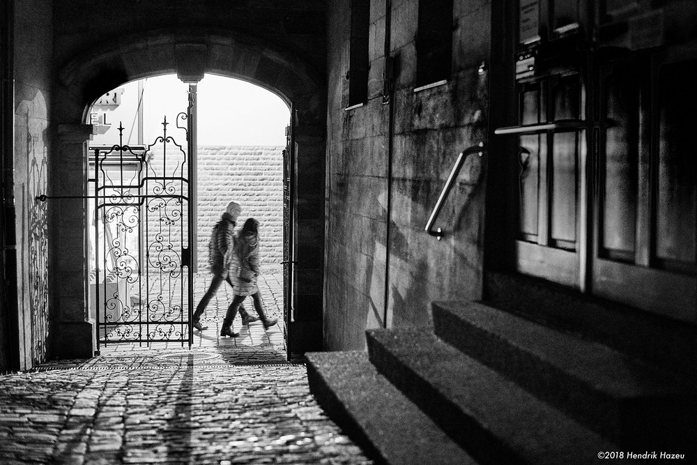 Two walkers before the gate. Nikon D850 & AF-S 58mm f/1.4G @f/2, 1/45 sec, 3200 ISO