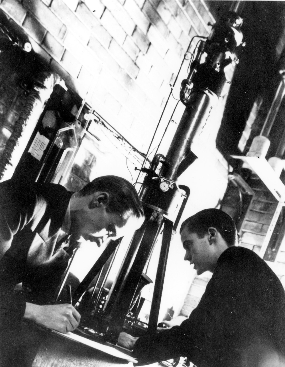 Figure 1: Prebus (left) and Hillier (right) working on their electron microscope in 1938. (Photo credit: https://www.physics.utoronto.ca/physics-at-uoft/history/the-electron-microscope/Web%20Image_1C.jpg)