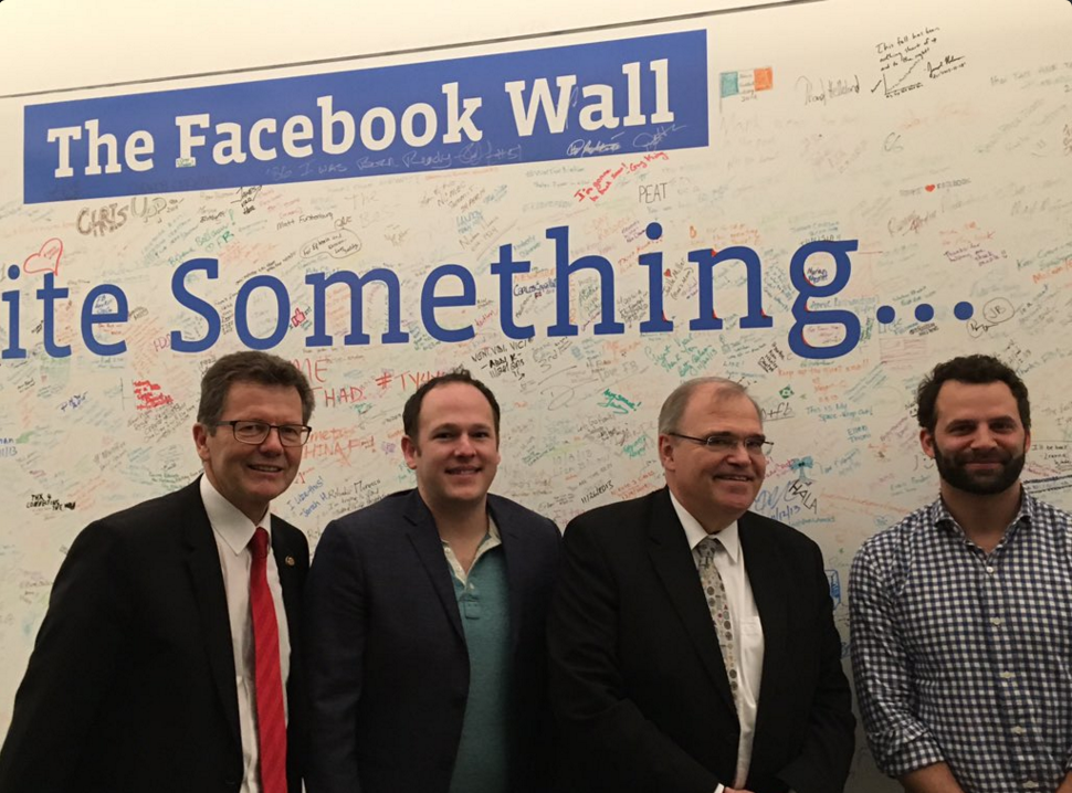 Ambassador Waldner, Minister Brandstetter and Facebook officials in front of the Facebook wall.