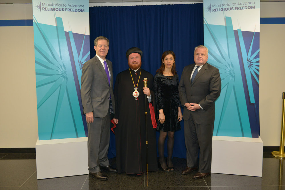 U.S.  Ambassador at Large for International Religious Freedom Sam Brownback,  Archbishop Mor Nicodemus, Nadia Murad, and Deputy Secretary of State  John J. Sullivan at the Ministerial to Advance Religious Freedom at the  U.S. Department of State in Washington, D.C. on July 25, 2018.  [State  Department photo/Public Domain].