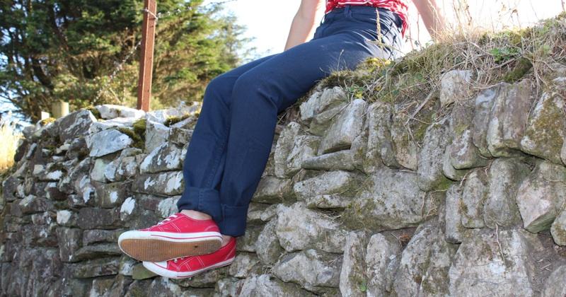 American Apparel Slim Slack Jeans Model Sat on Wall.jpg