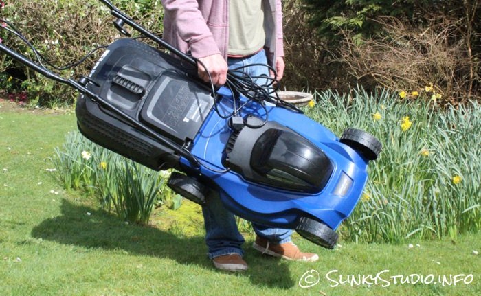 Einhell BG-EM 1437 Electric Lawnmower Being Carried in front of Flower Meddow.jpg