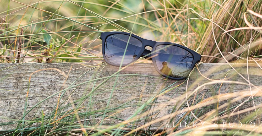 SunGod Classics² Sunglasses Hanging on Wood in Grass.jpg