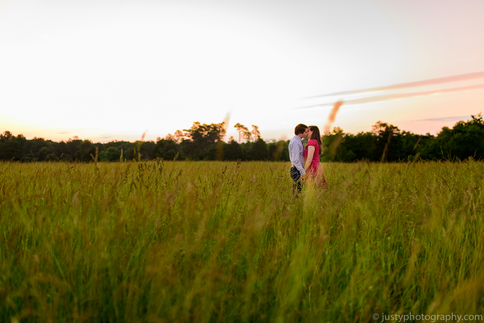 Engagement couple standing in field. Sunrise session.