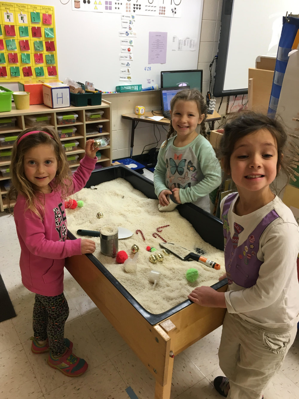 """playing with """"snow"""" in the sensory table. It's white rice and Christmas ornaments."""