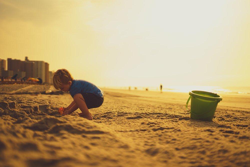 boy squatting on beach.jpg