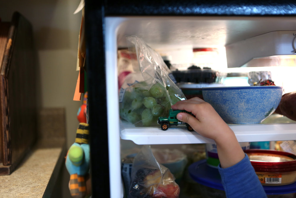 Sam plays with a toy car in the refridgerator.
