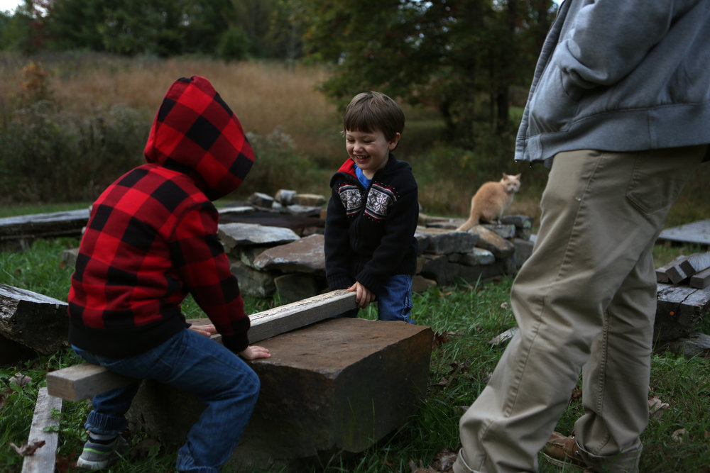 Louis, left, and Sam use a plank of wood in the yard as a make-shift seesaw.