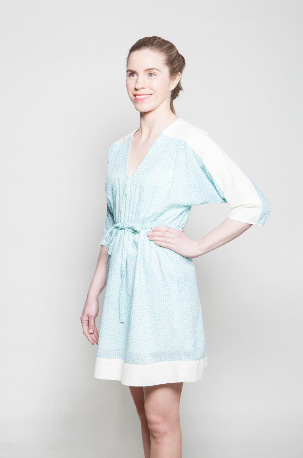 Dress has a thin fabric belt on a waist and wide fabric panels on shoulders and on a hem.