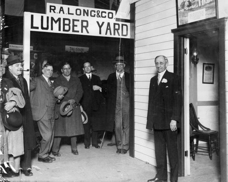 Long stood in 1930 before a mock-up of the first office of his lumber business, which had started in Columbus, Kan., 55 years earlier.