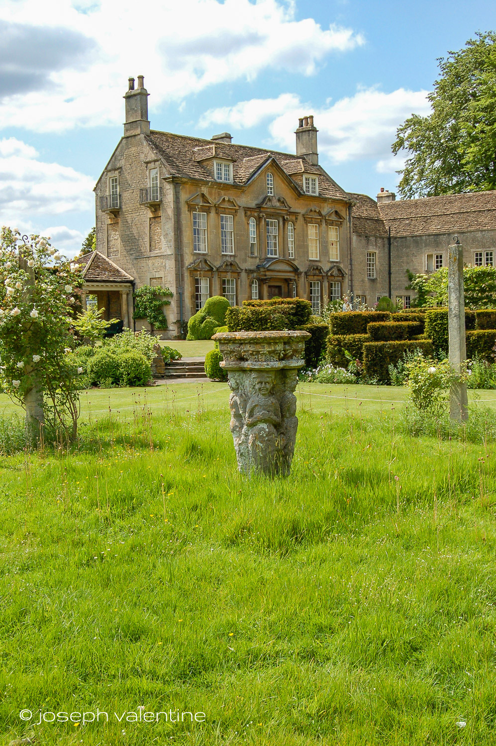 Sections of uncut grass alternate with mown turf in front of the manor house at The Courts in England.