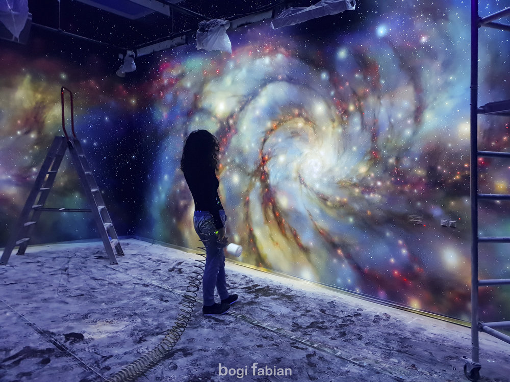 Bogi Fabian Glowing mural Ultraviolet Blacklight Art Universum Galaxy interior design Glowinthedark GLOWING GALAXY MURALS - CONNECTING YOU TO THE UNIVERSE The worlds most advanced 3D color glow prints. Multiluminous Glowing Canvas technology Worlds first GLOWCANVAS Imagine a mesmerizing window into the universe from the comfort of your home. Glow-In-the-Dark Artwork. Transform your ceiling into a stunning cosmic scene with a milky way mural Breathtaking Milky way STAR MURALS Glow Mural