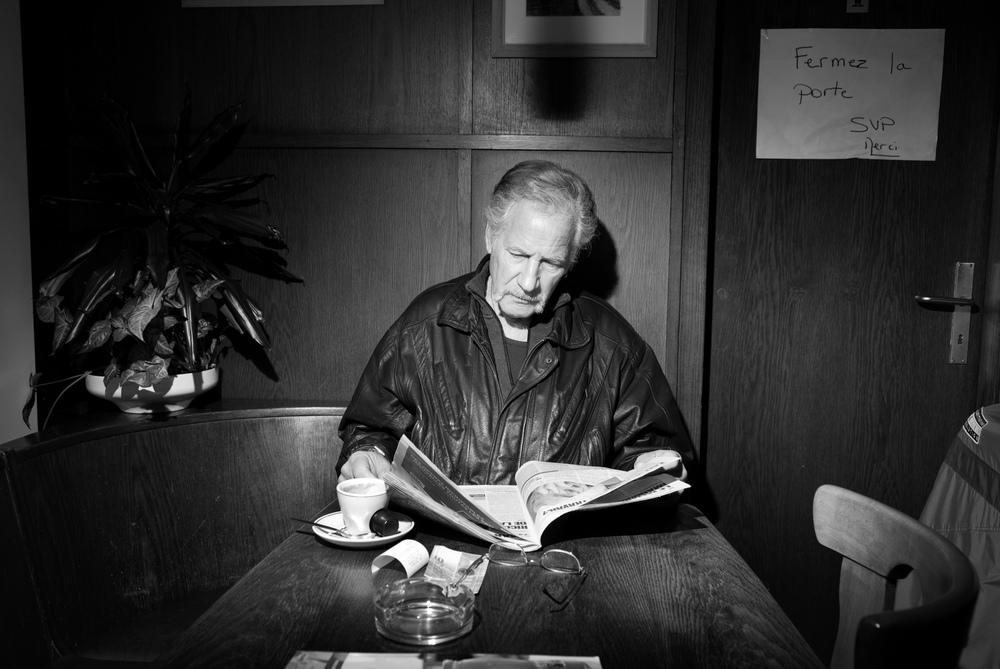 Un lecteur de journaux, tôt le matin dans un café.