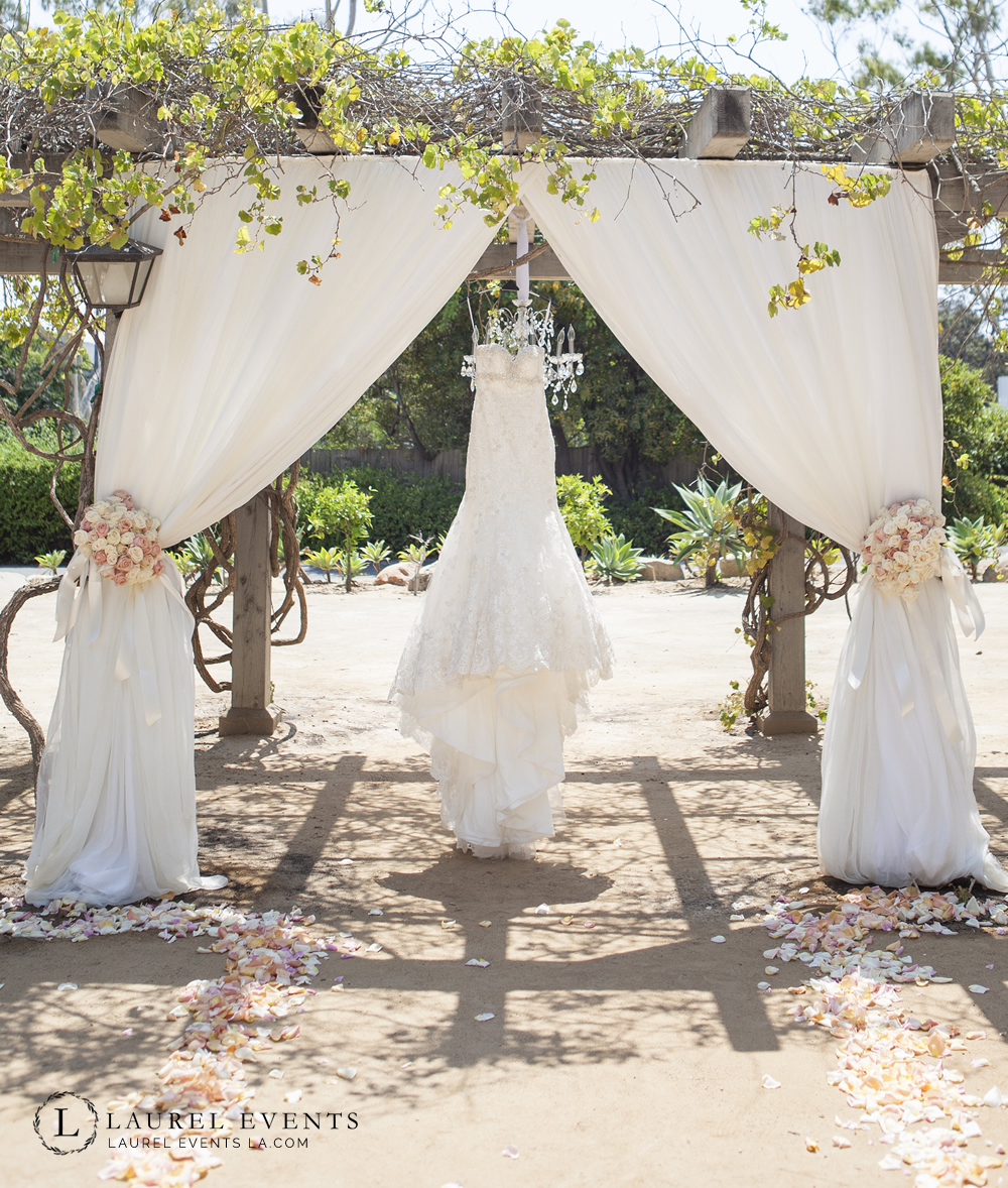 Rustic Chic wedding chuppah with hanging chandelier and floral tie backs.