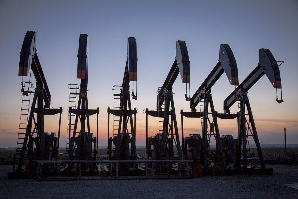 Oil wells at sunset in rural Oklahoma.