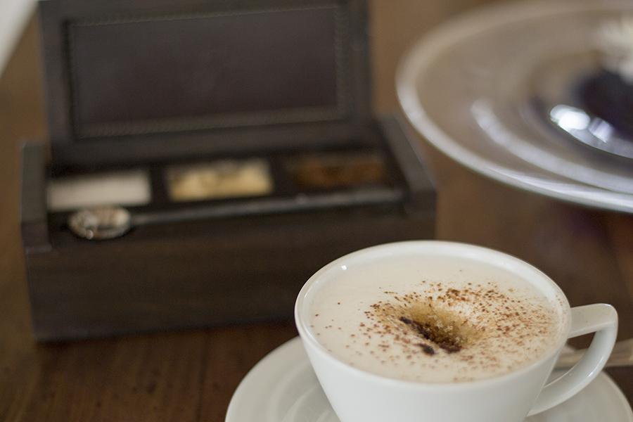 Cappucino presented with a trio of sugars in a handcrafted wooden box