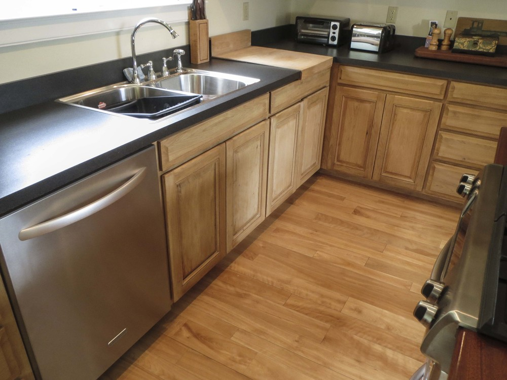 The finished product incorporates custom cabinetry that brings out the wood tones in the floor.