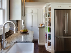 Notice the floor to ceiling cabinetry including a drawer above the refrigerator, the shallow depth of the counter, and the tall open shelving.  (Mark McCauley for HGTV)