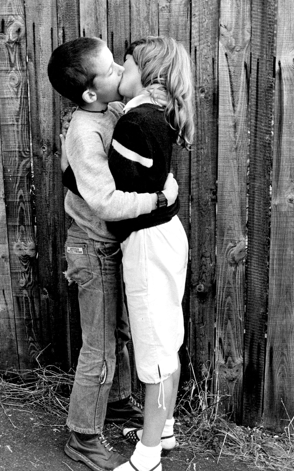 Two kids kissing by wooden fence High Wycombe, UK, 1980's. © Gavin Watson / PYMCA