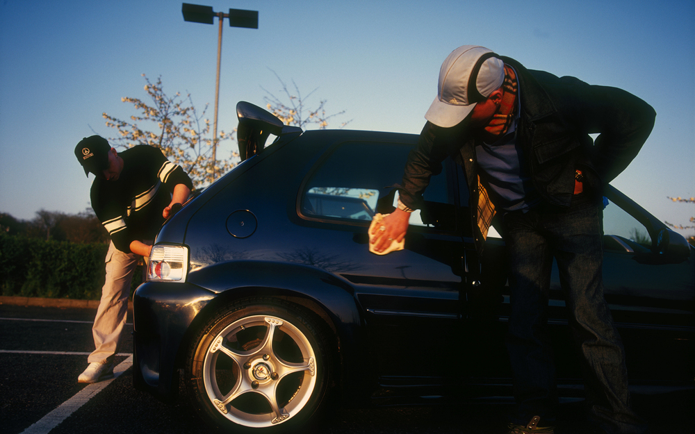 Two men polishing a customised car, At boy racer meeting at clackett lane service station, M25, UK, 2000'S   © Naki / PYMCA