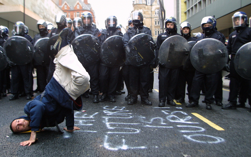 A protester busting a move in front of a line of Riot Police, With Graffiti, 'The Future Is Ours' Written on the road, Mayday Riots, London 2001 © Lee Jones / PYMCA