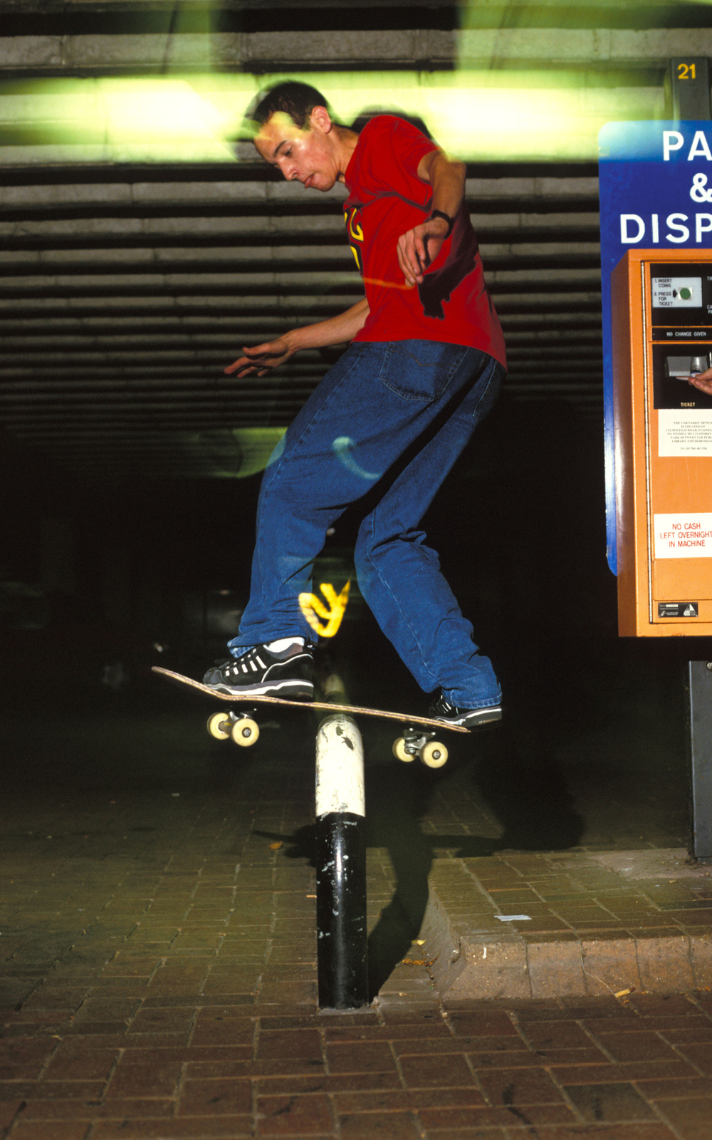 Skater, Robert Jaye, doing a rail-slide on a metal barrier in a car park, UK, 2000's . ©  Styley  / PYMCA