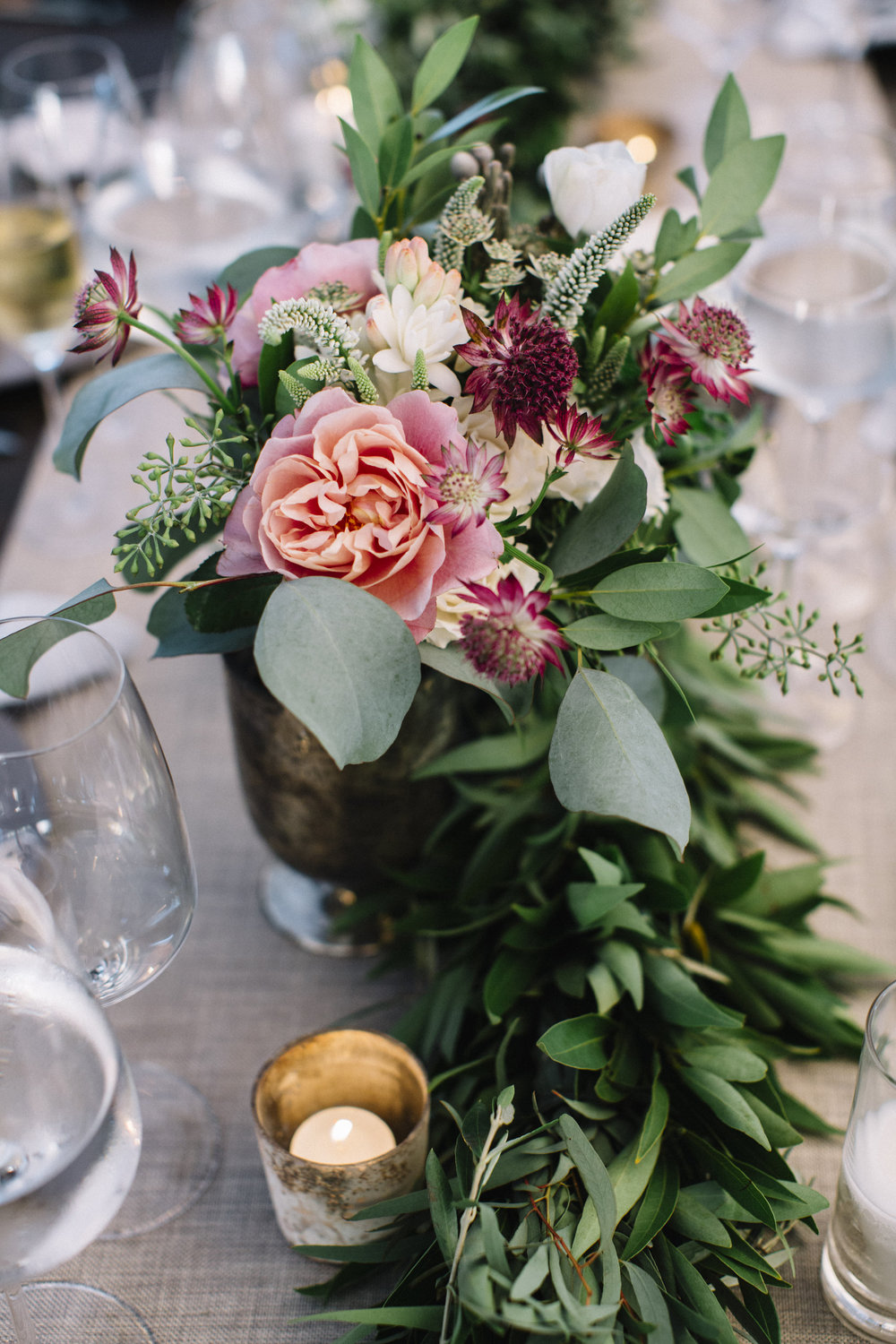 Shimmery votives, greenery garland, and composed centerpieces create a vibrant runner for the length of your table | Design by Venn Floral | Photo by Lucille Lawrence