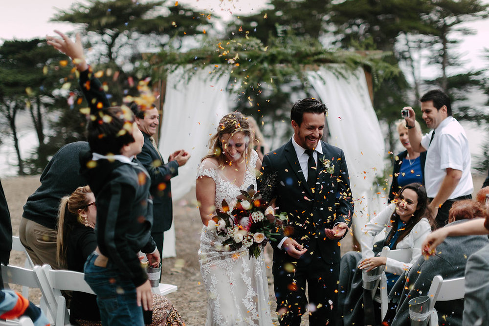 Just married! Celebratory flower petals are tossed by guests at this Straus Home Ranch wedding with Venn Floral & Levi Tijerina.