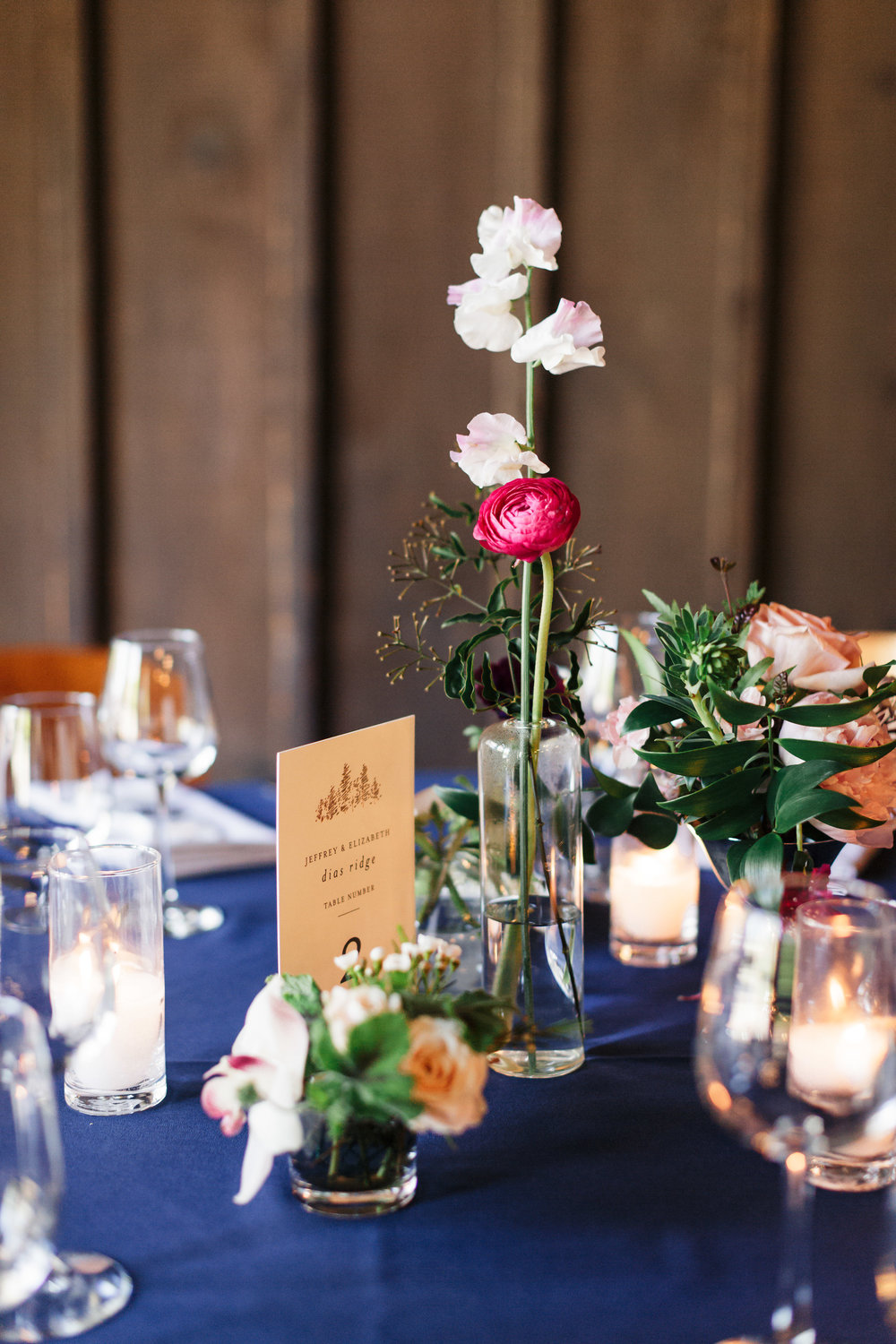Bud vases, vintage silver compotes, and candles centerpiece vignette at The Outdoor Art Club in Mill Valley, California with Torrey Fox Photography, Venn Floral, Sage Catering, and Oh Splendid Day.