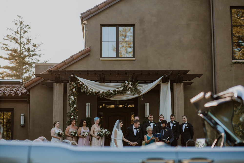 Healdsburg wedding ceremony photographed by Gretchen Gause Photography. Floral garland and fabric draping ceremony backdrop by Venn Floral.