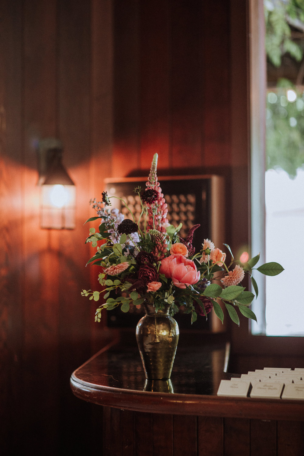 Escort display with vintage brass and colorful flowers by Venn Floral photographed by Gretchen Gause in Healdsburg, California at Villa Chanticleer.
