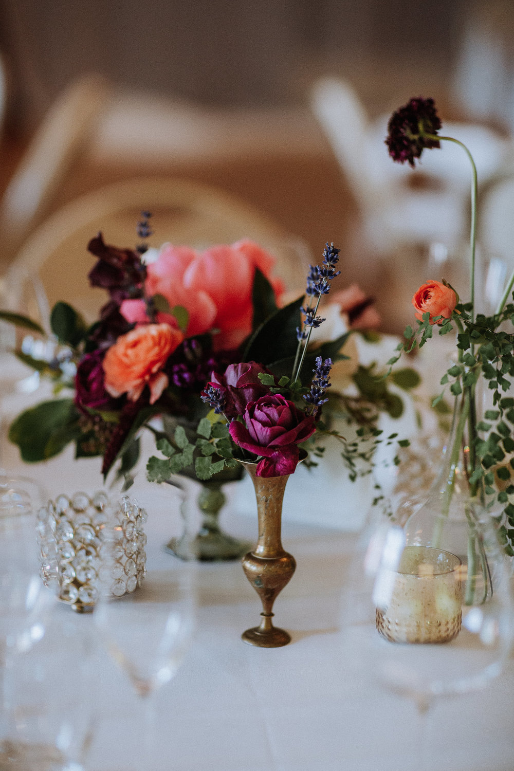 Colorful centerpieces with bud vases, vintage brass, and candles by Venn Floral, photographed by Gretchen Gause in Healsdsburg, California.
