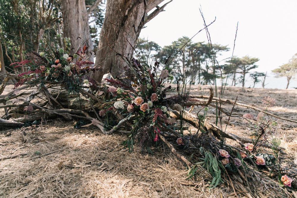 Sculptural and wild ceremony backdrop with branches and seasonal flowers on the Tomales Bay