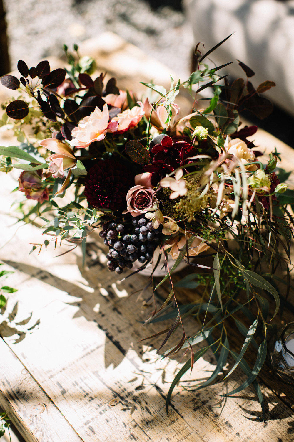 Seasonal floral design by Venn Floral with black grapes, koko loko garden rose, eucalyptus and orchids for a Sonoma Coast ranch wedding photographed by Lucille Lawrence.