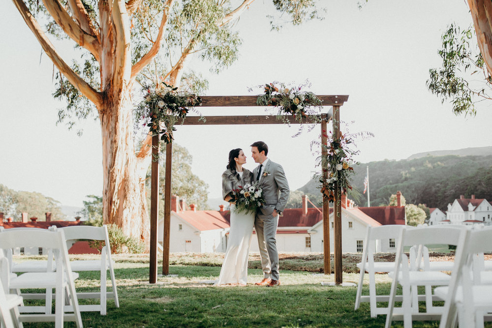 Cavallo Point wedding ceremony flowers by Venn Floral photographed by Ryan Chard Smith. Wooden ceremony structure with asymmetrical florals and greens.