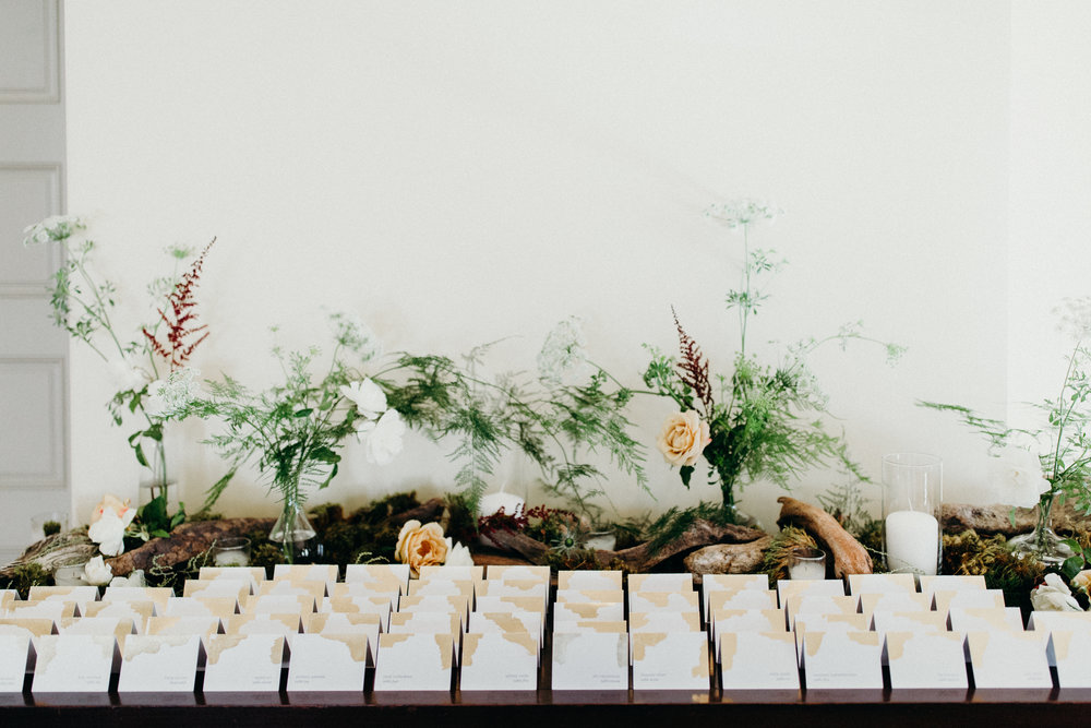 Natural and woodsy escort card display with driftwood, bud vases and candles by Venn floral with gold leaf escort cards by Love Notes Paper. Photography: Ryan Chard Smith