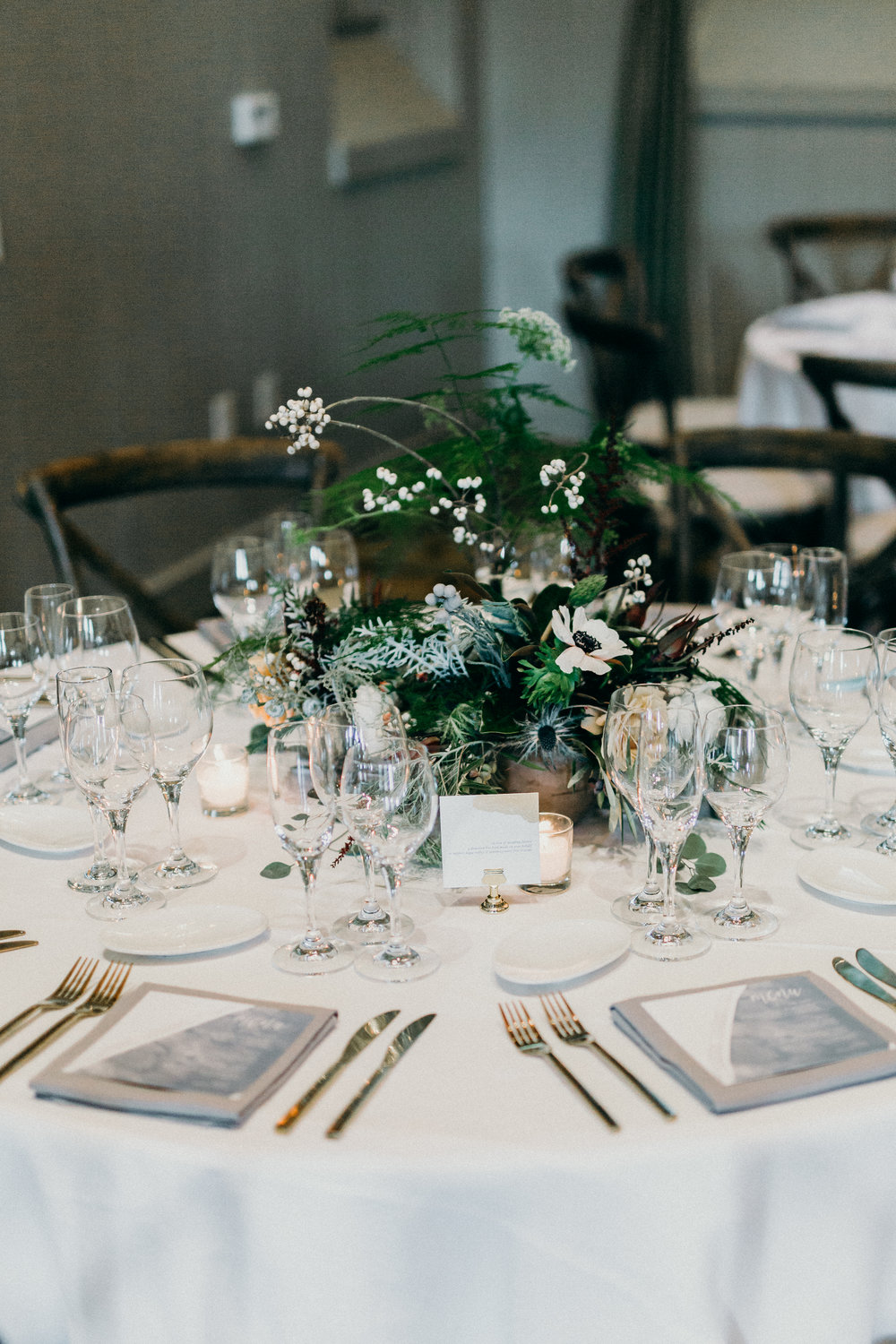 Green, white, and silver centerpiece flowers by Venn Floral with Anemones, Eryngium, and Ferns photographed by Ryan Chard Smith at Cavallo Point.