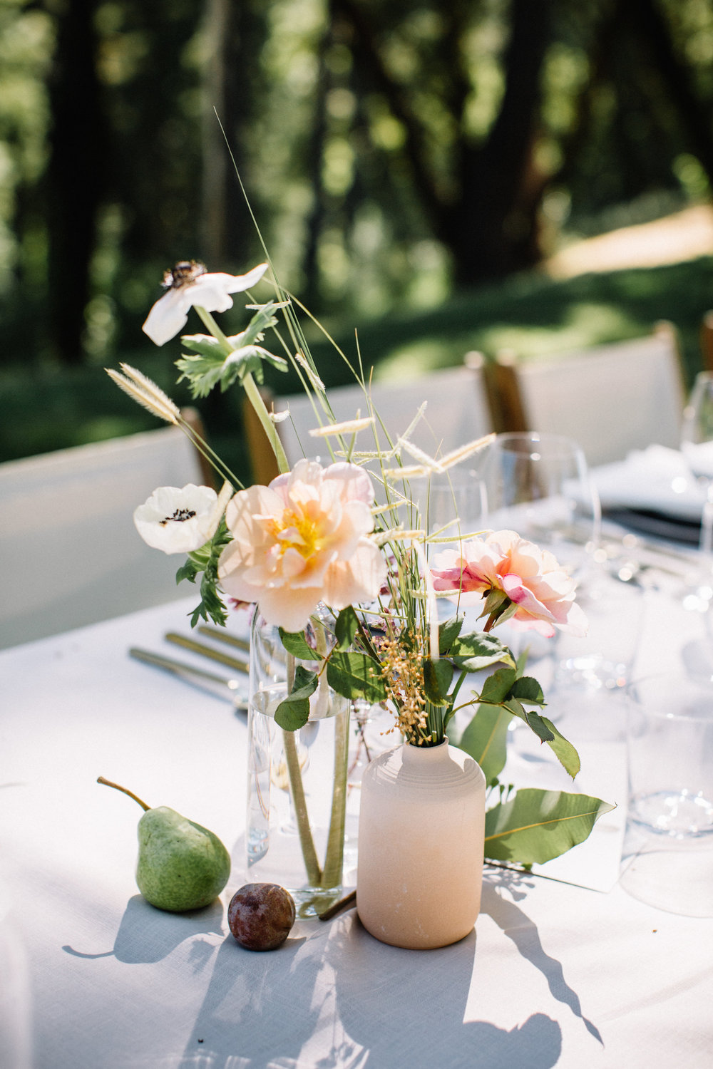 Ceramic bud vases and clusters of Summer fruit and flowers by Venn Floral at Wild Iris Retreat photographed by Lucille Lawrence in Philo, California.