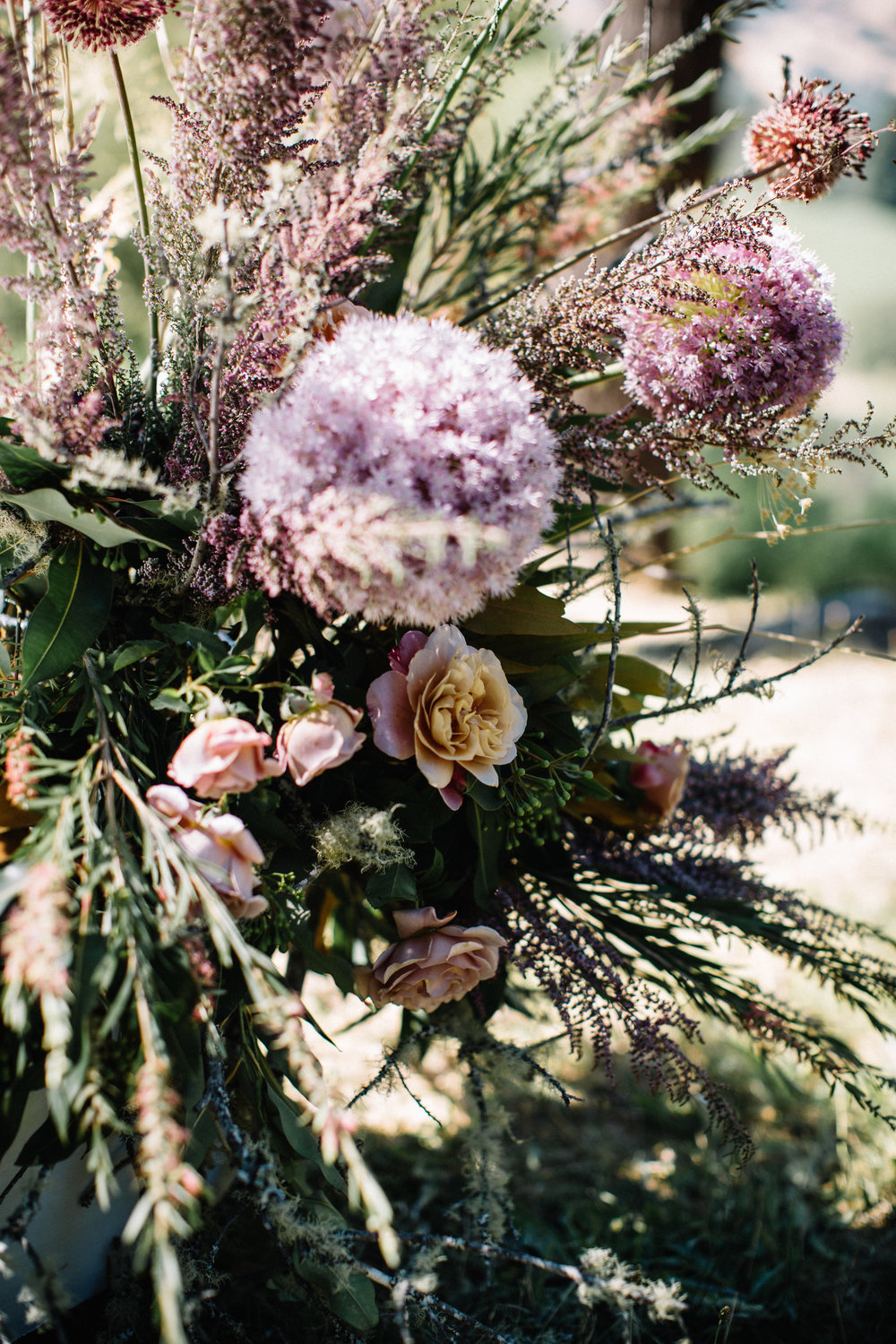 Allium, garden rose and pink bottle brush installation by Venn Floral at Wild Iris Retreat photographed by Lucille Lawrence in Philo, California.