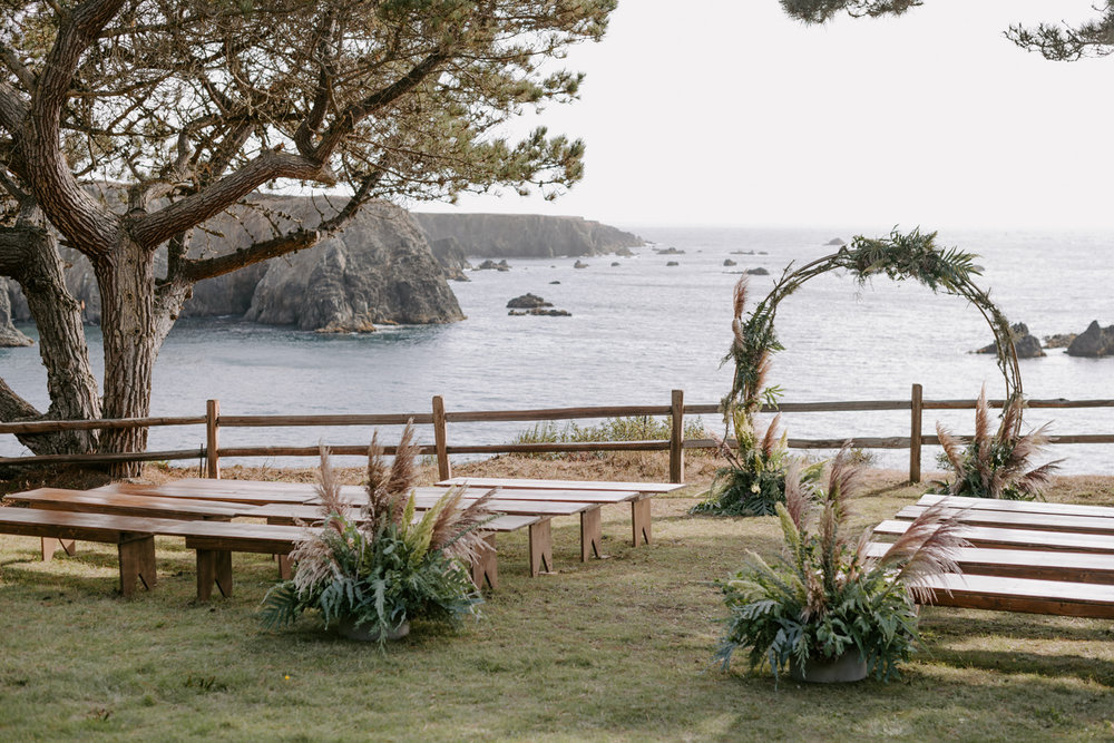 Circular ceremony arch with ferns, pampas grass, and mossy branches by Venn Floral at Heritage House Resort photographed by Kristen Marie Parker for a Mendocino Coast wedding.