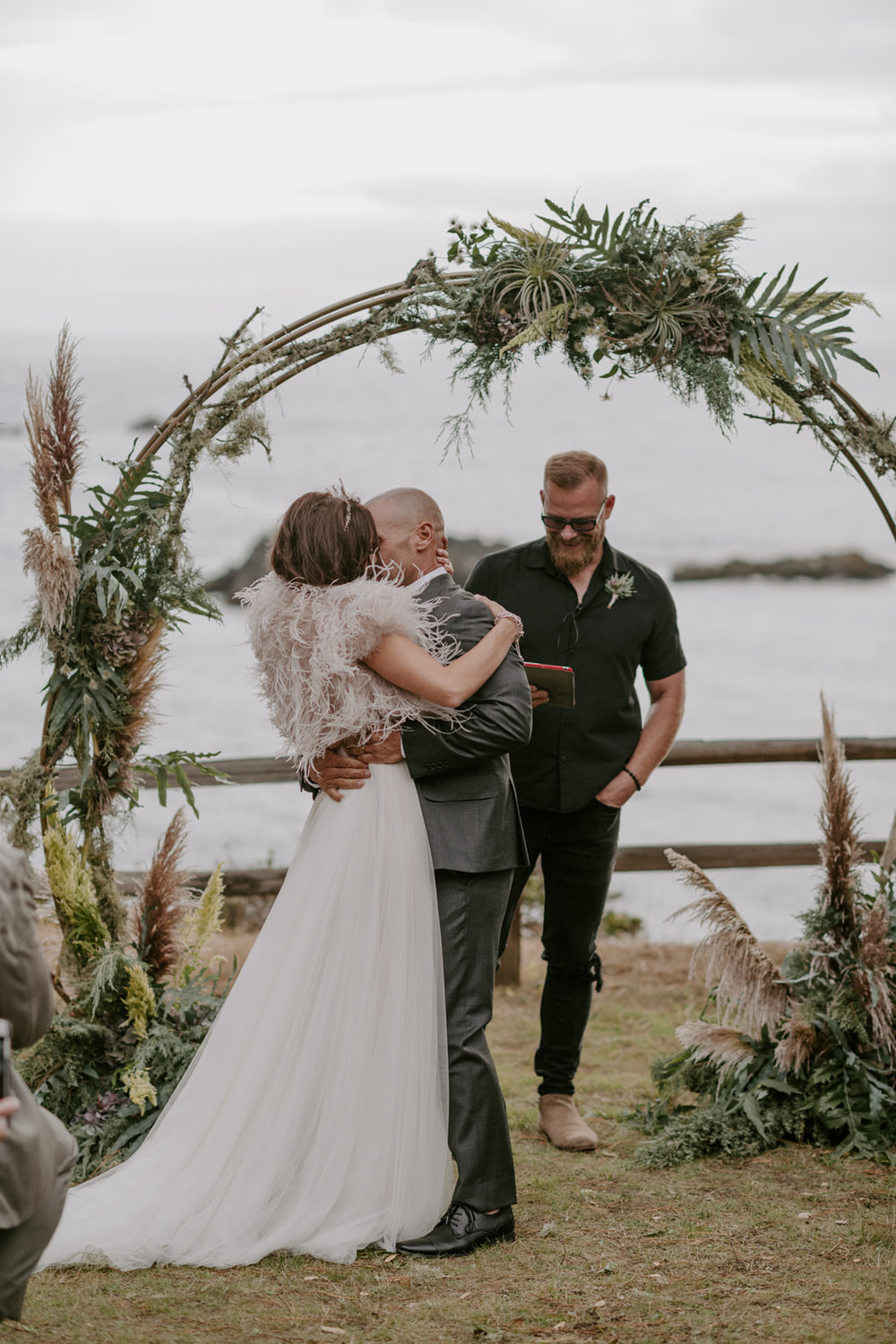 Sultry oceanside nuptials with a circular ceremony arch with ferns, pampas grass, and mossy branches by Venn Floral at Heritage House Resort photographed by Kristen Marie Parker.