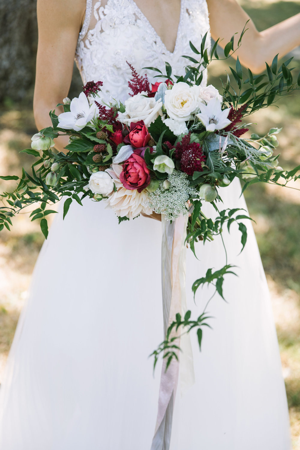 Wild bridal bouquet with roses, vines, and berries in coral red, cream and green by Venn Floral at Olympia's Valley Estate photographed by The Edges.