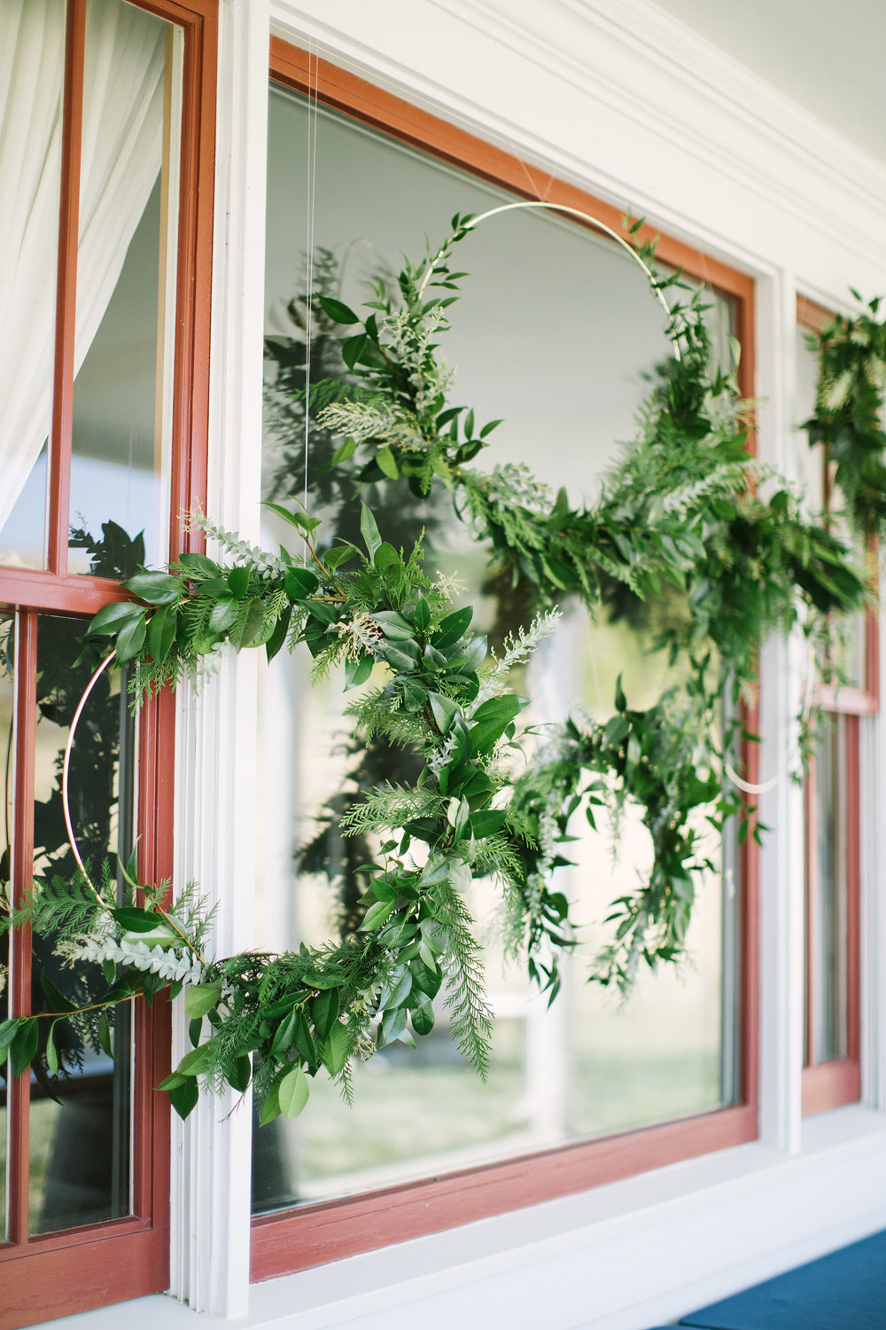 Hanging greenery wreaths on gold hoops by Venn Floral at Olympia's Valley Estate with A Savvy Event photographed by The Edges