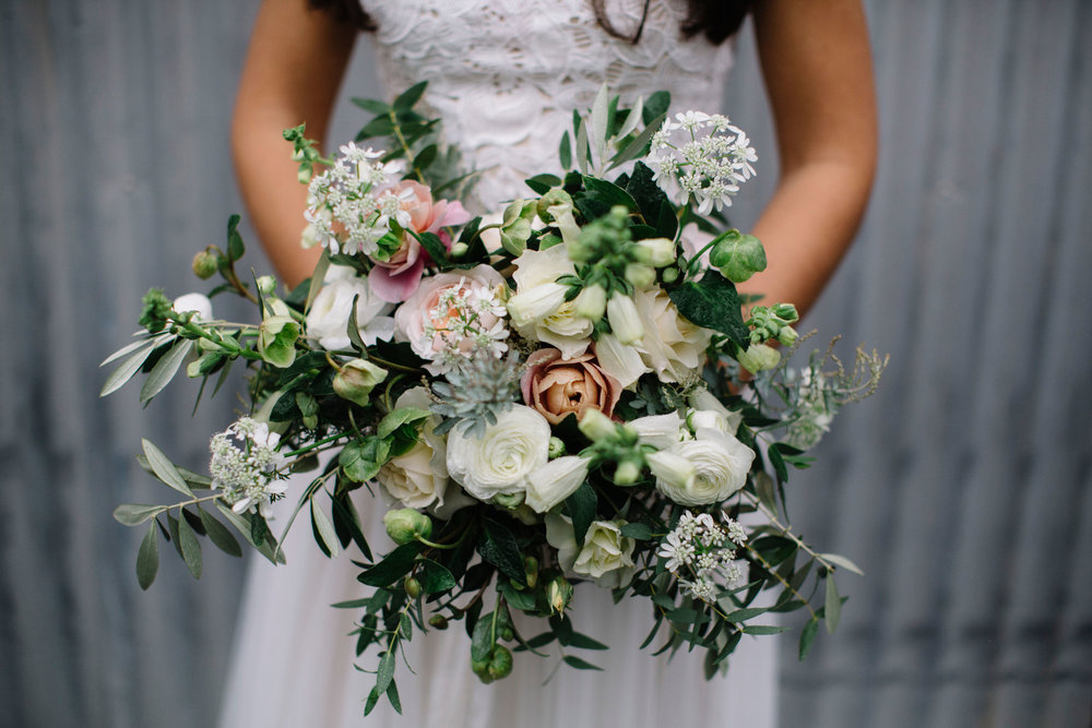 Organic and textured bridal bouquet with light airy flowers in shades of white, peach, and green by Venn Floral at Ru's Farm in Healdsburg photographed by Lucille Lawrence